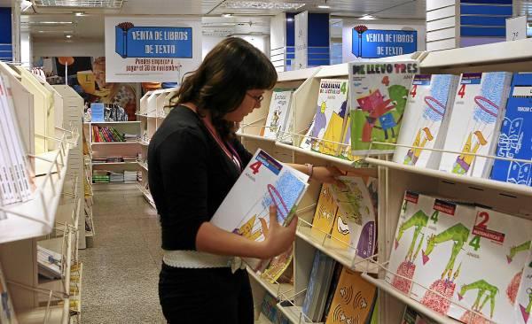 Una joven coge libros de texto de una estantería de un centro comercial. / El Correo