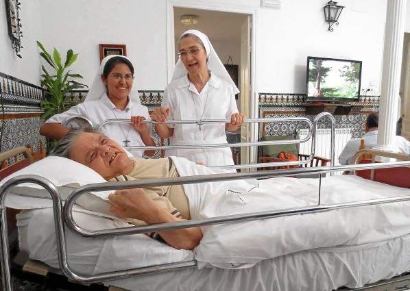 La madre superiora, a la derecha, y otra de las religiosas de la institución tratan de arrancarla una sonrisa a 'Fernandito', unos de los acogidos más veteranos. / El Correo
