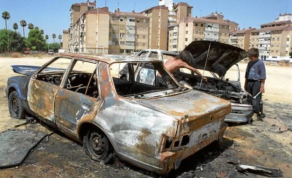 Imagen de archivo de dos coches quemados y abandonados en una explanada de las Tres Mil Viviendas. / Pepo Herrera