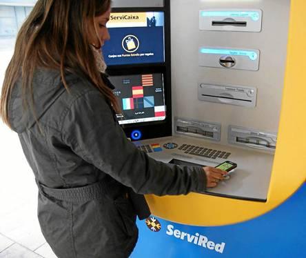Una usuaria acerca su teléfono móvil al terminal para operar sin necesidad de tarjeta electrónica. / EL CORREO