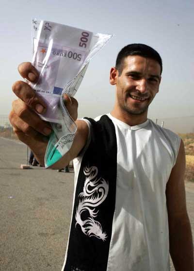 Uno de los chabolistas desalojados de Los Bermejales muestra el sobre con los billetes de 500 euros. / Pepo Herrera