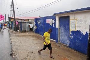 Un hombre liberiano camina por West Point,  donde los paciente de ébola huyeron tras un ataque y saqueo por parte de los manifestantes en Monrovia. / AHMED JALLANZO (EFE)