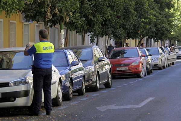 Un trabajador de GES de la empresa Aussa, adjudicataria de la zona azul, revisa los tickets de uno de los coches. /