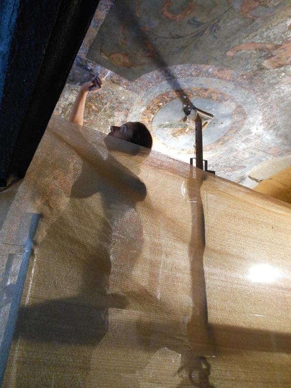 Una restauradora, trabajando ayer en las pinturas murales de la bóveda del patio bajo del Crucero.