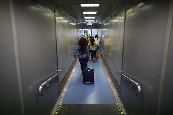 Dos hermanas sevillanas caminan por el túnel de embarque en el aeropuerto de San Pablo tras encontrar trabajo fuera. / REUTERS