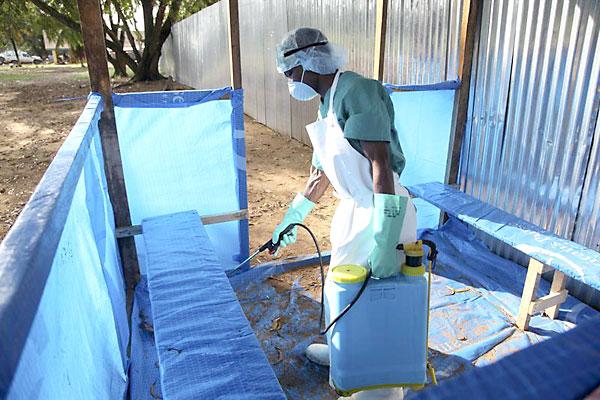 Una enfermera liberiana aplica un líquido desinfectante para prevenir la propagación del virus del ébola. / EFE