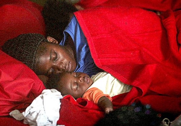 Una madre con su hijo duerme en uno de los pabellones en Tarifa. / EFE