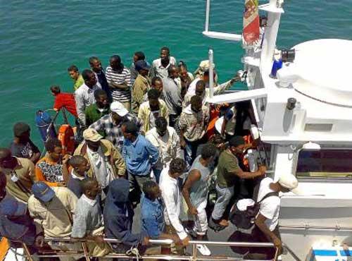 Un grupo de inmigrantes irregulares a bordo de un barco de los guardacostas a su llegada a la isla de Lampedusa. / EFE