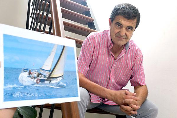 """Carlos Yáñez-Barnuevo, médico de 59 años, posa en Sevilla junto a la fotografía de su velero """"Ágata"""" en el que naufragó navegando en solitario. / EFE"""