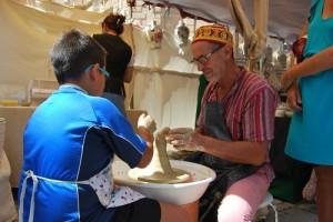 Antonio Bellido muestra cómo trabajar el barro a Jesús, un visitante de la feria. Foto: Laura López