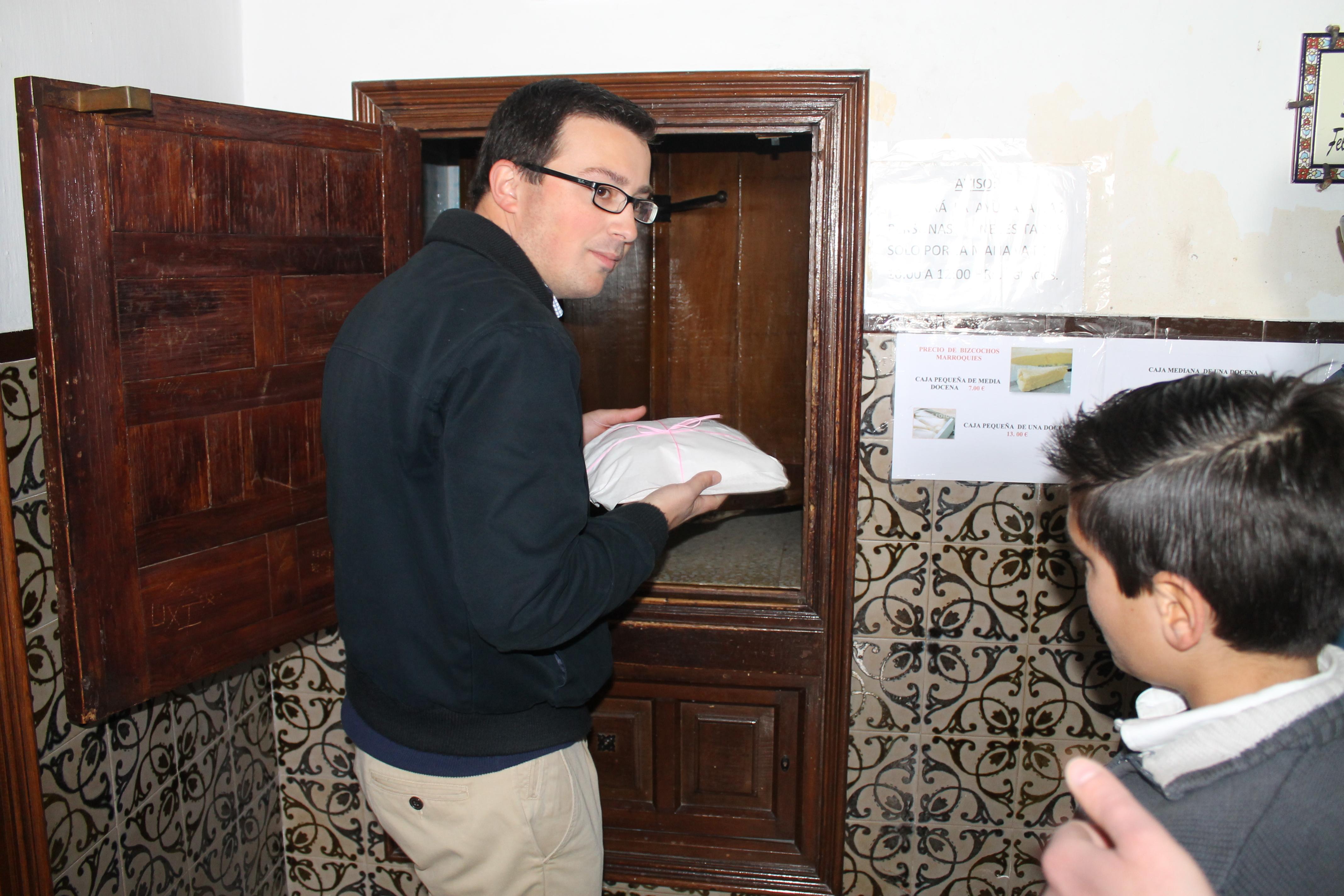 Un hombre recoge una bandeja de los célebres bizcochos marroquíes del torno del convento ecijano. Foto: M. R.