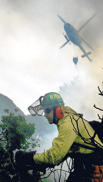 Un bombero trabaja en la extinción de un incendio. / Jorge Zapata (EFE)