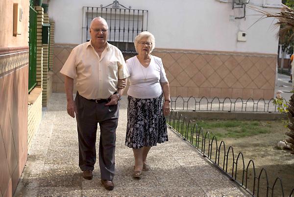 Fernando acompaña a Lina en cada uno de sus trayectos para evitar que se despiste, incluso dentro de la urbanización en la que viven de toda la vida y donde también residen dos de sus cinco hijas. / Fotos: J. M. Paisano