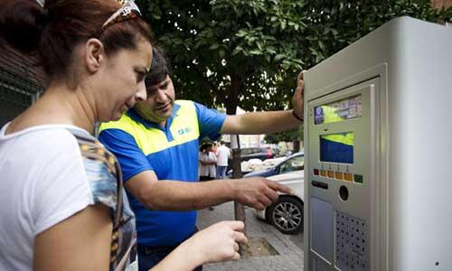 Un trabajador de Aussa explica las instrucciones del parquímetro a una usuaria de la zona azul de Bami. Foto: Pepo Herrera
