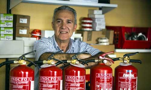 Simón Torreglosa, en su establecimiento de extintores, el más antiguo de Sevilla, en la calle Amor, número 5. / Foto: Carlos Hernández
