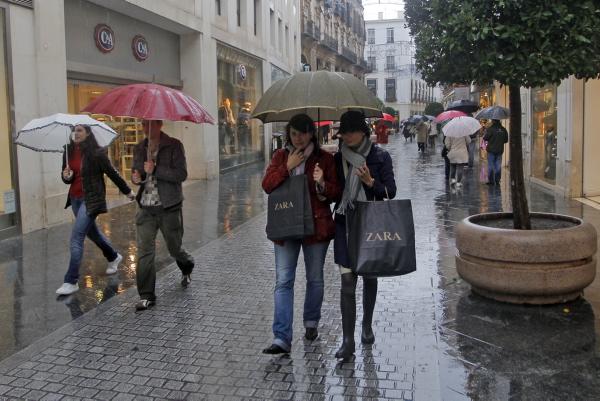 Compras navideñas en el centro en un día de lluvia.