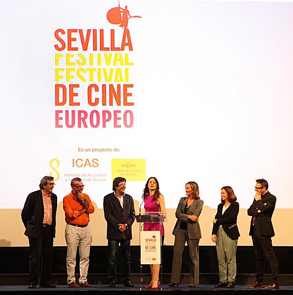 Cuca Escribano se dirige a los asistentes ante Herrero, Antonio Pérez, Gómez Pereira, Sánchez Estrella, Lorena G. Olivares y Cienfuegos. / El Correo