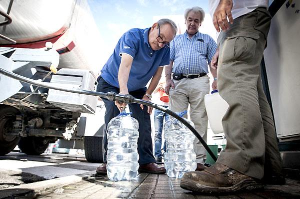 Varios del barrio de Loreto se abastecen de agua de camiones cisterna. / EFE