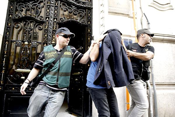 Dos agentes de la Guardia Civil escoltan a un detenido en Valencia durante la operación Púnica. / EFE
