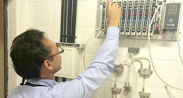 Un técnico antenista adaptando un amplificador monocanal de un edificio. / R.M.