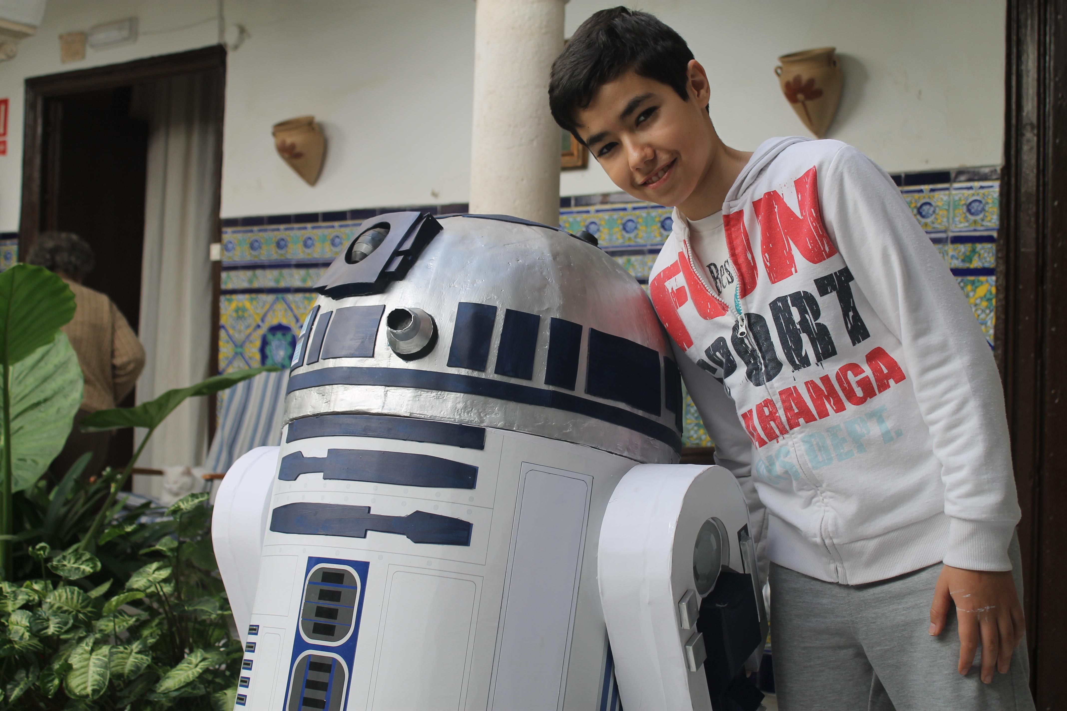 Un joven posa junto a un R2-D2 a tamaño natural, ubicado en un típico patio ecijano del centro de la ciudad. Foto: M. R.