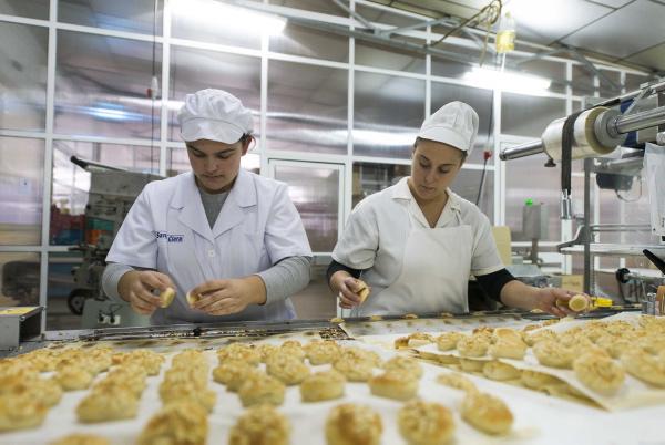 BelénSánchez y Chari Blanco, trabajadoras de la fábrica de mantecados Santa Clara, mientras manipulan los dulces. / J.M.Paisano
