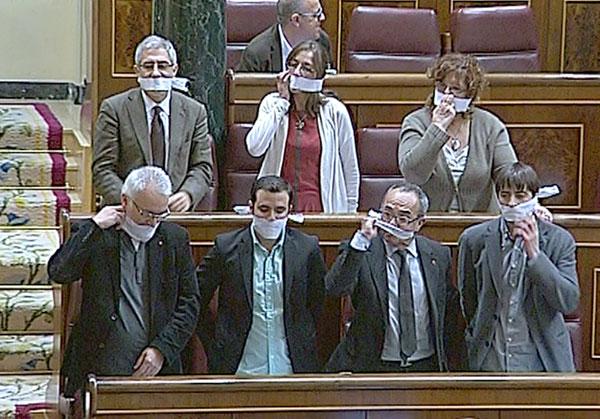 Imagen tomada de televisión de los siete diputados de Izquierda Plural, que se han amordazado la boca en protesta por la aprobación de la ley. / EFE