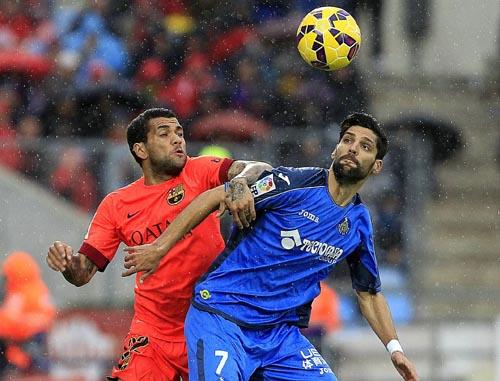 El defensa brasileño del Barcelona Daniel Alves pelea un balón con el centrocampista del Getafe Ángel Lafita. EFE/Víctor Lerena