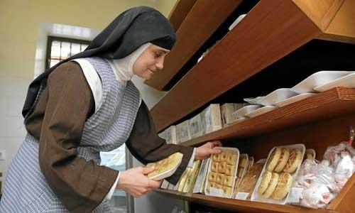 Sor Angélica repone en las estanterías del despacho algunas de las especialidades confiteras del convento de Santa María Jesús. Foto: José Luis Montero