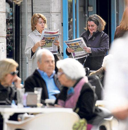 Dos lectoras consultan sus ejemplares de El Correo de Andalucía en plena calle. / Pepo Herrera
