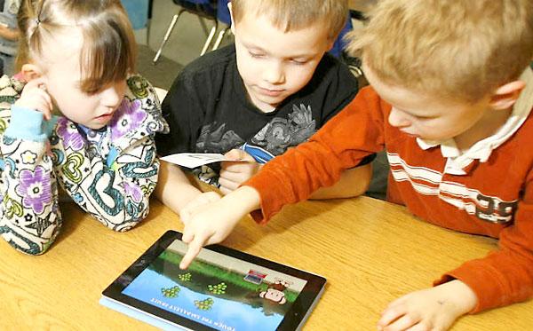Unos niños juegan con una tableta. / El Correo