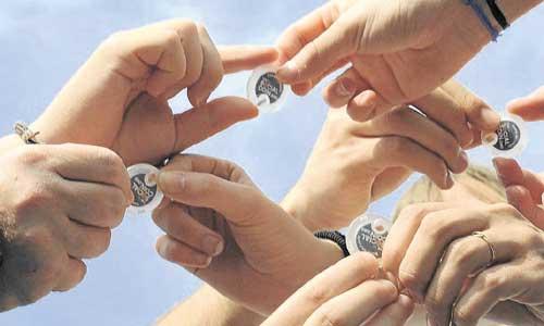 Imagen en la que personas intercambian monedas solidarias y una ilustración sobre cómo usarla.