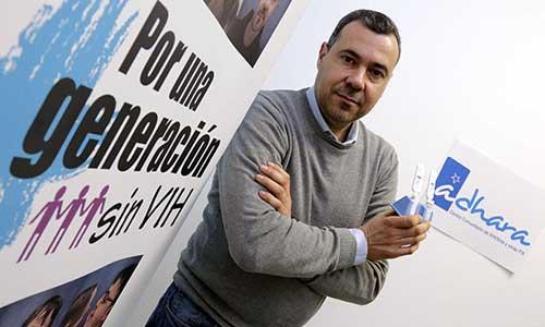 El voluntario de la asociación sevillana Adhara, Jesús García, posa junto a un kit de detección de VIH/Sida por saliva. / José Luis Montero