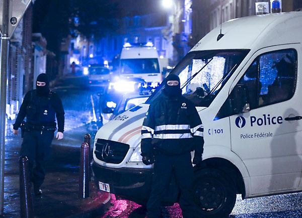 Varios antidisturbios vigilan los accesos cerrados a la calle donde se ha llevado a cabo una operación antiterrorista en la ciudad de Verviers. / EFE
