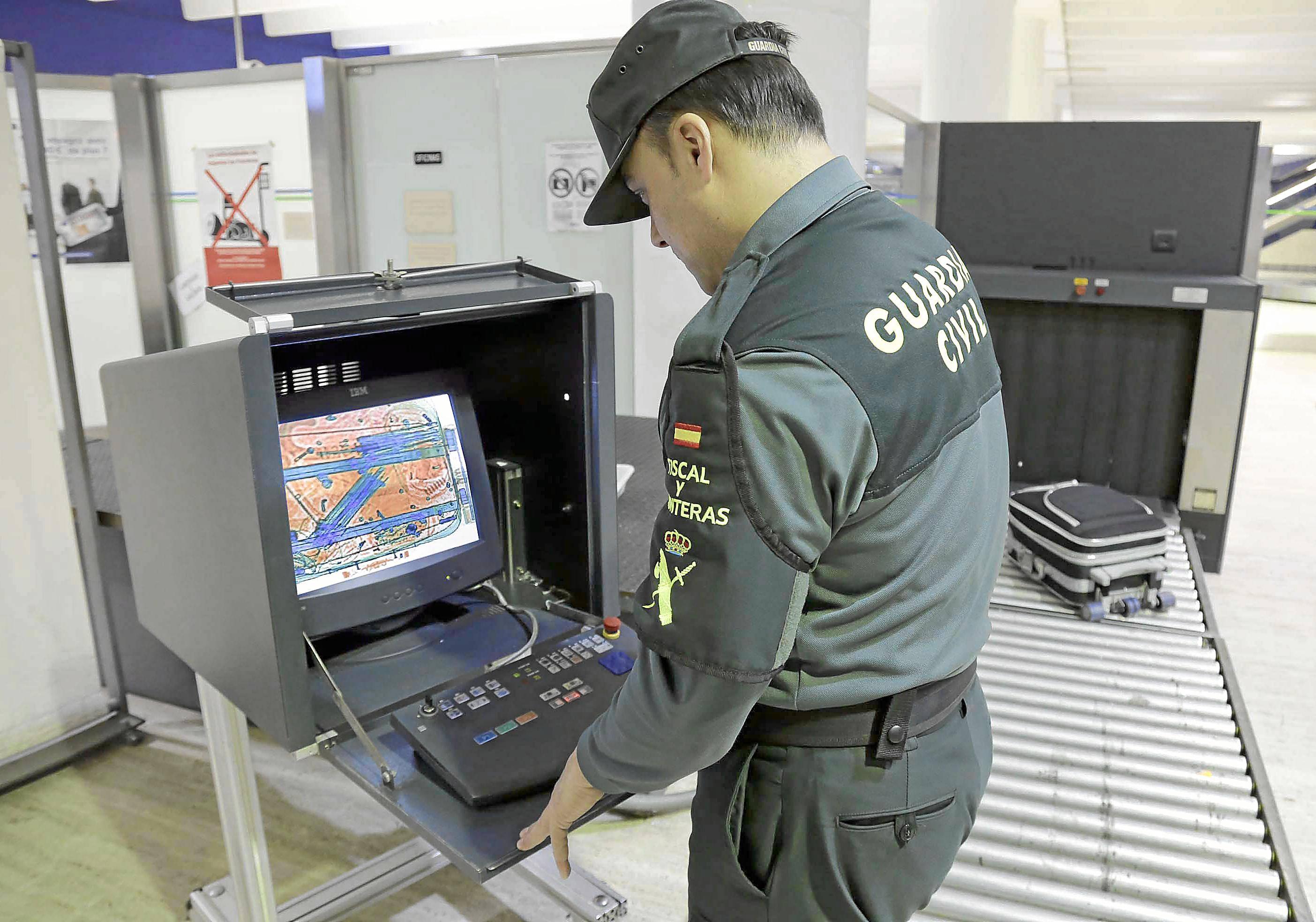 un agente de la Guardia Civil pasa una maleta por el escáner para comprobar si lleva droga o algún objeto prohibido. / José Luis Montero