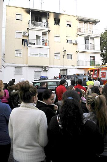 Decenas de personas se agolpan junto a la vivienda de la calle Matallana de Lora del Río (Sevilla) donde se ha producido un incendio. / EFE