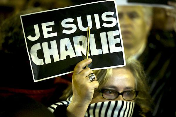 """Una mujer sostiene un cartel en el que se lee """"Yo soy Charlie'. / EFE"""