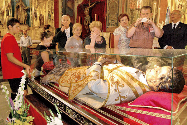 Un grupo de fieles y curiosos contemplan la imagen de Don Bosco. / S.C.
