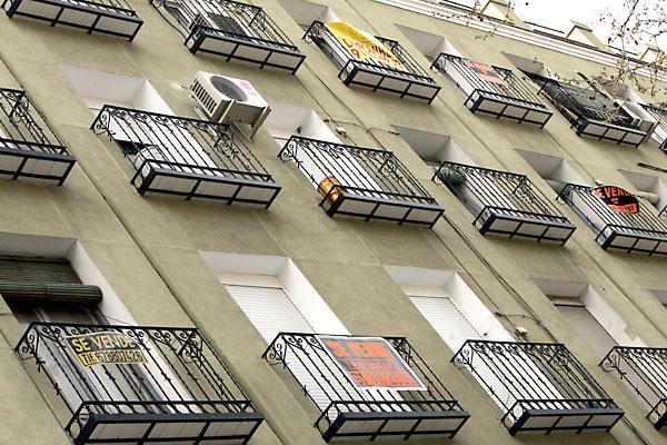 Balcones con carteles que anuncian la venta de varios pisos en un mismo bloque de viviendas. / El Correo