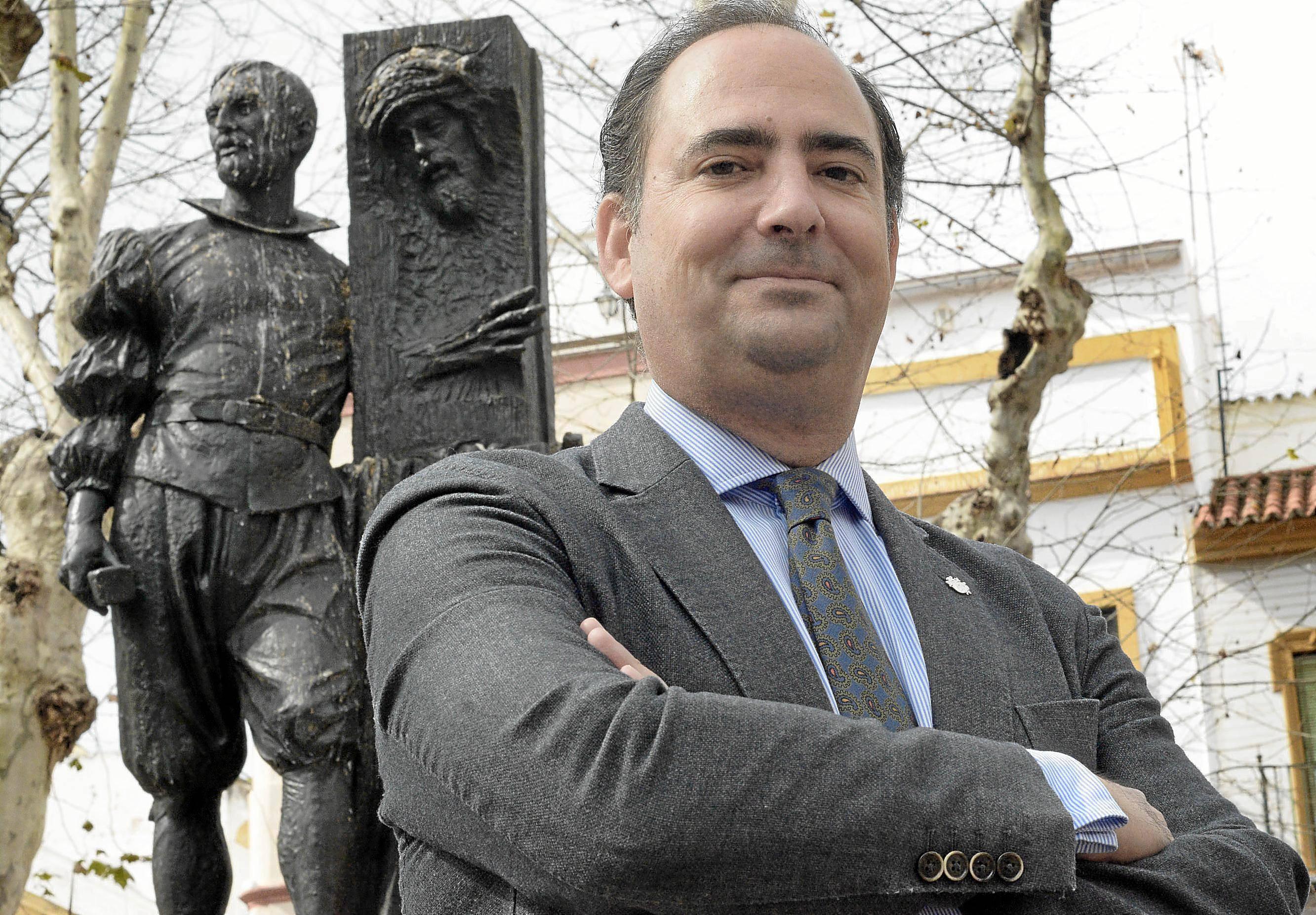 Félix Ríos, hermano mayor del Gran Poder, posa junto al monumento levantado a Juan de Mesa en la plaza de San Lorenzo. / Manuel Gómez