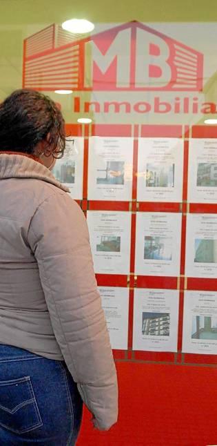 Una mujer, ante la publicidad de una inmobiliaria. / Gregorio Barrera