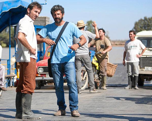 Alberto Rodríguez da instrucciones al actor Antonio de la Torre (izquierda) montado en la barcaza de Coria durante el rodaje de La Isla Mínima. / El Correo