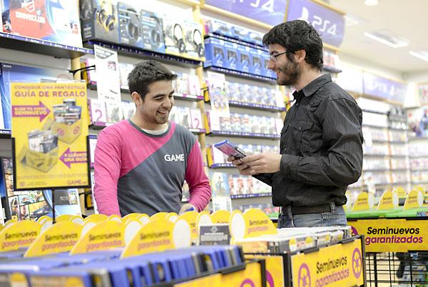 Lucas García, jefe de sección en la tienda Game del centro comercial Nervión Plaza de Sevilla, asesora a David Durán, uno de clientes, en la búsqueda de un videojuego. / Inma Flores