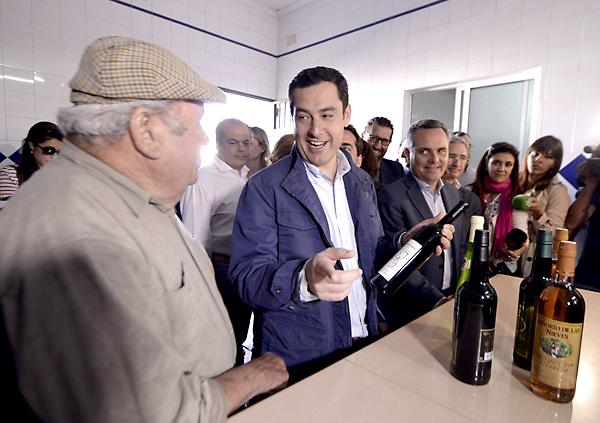 El candidato del PP a la presidencia de la Junta de Andalucía, Juanma Moreno, habla con un hombre durante la visita realizada hoy a una cooperativa en la localidad sevillana de Los Palacios, donde ha hablado con los trabajadores del programa con el que su partido se presenta a las próximas elecciones autonómicas del 22 de marzo. EFE/Rafa Alcaide